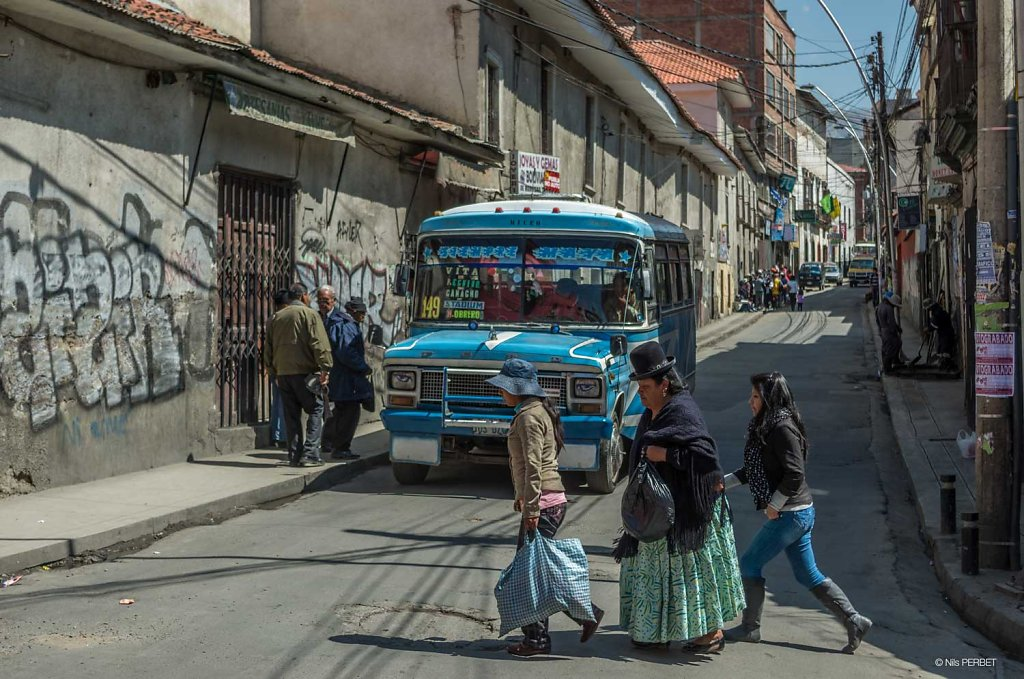 Traditionally dressed women crossing a street front of a bus at